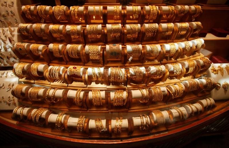 Gold inches down on robust dollar; Italy crisis curbs losses