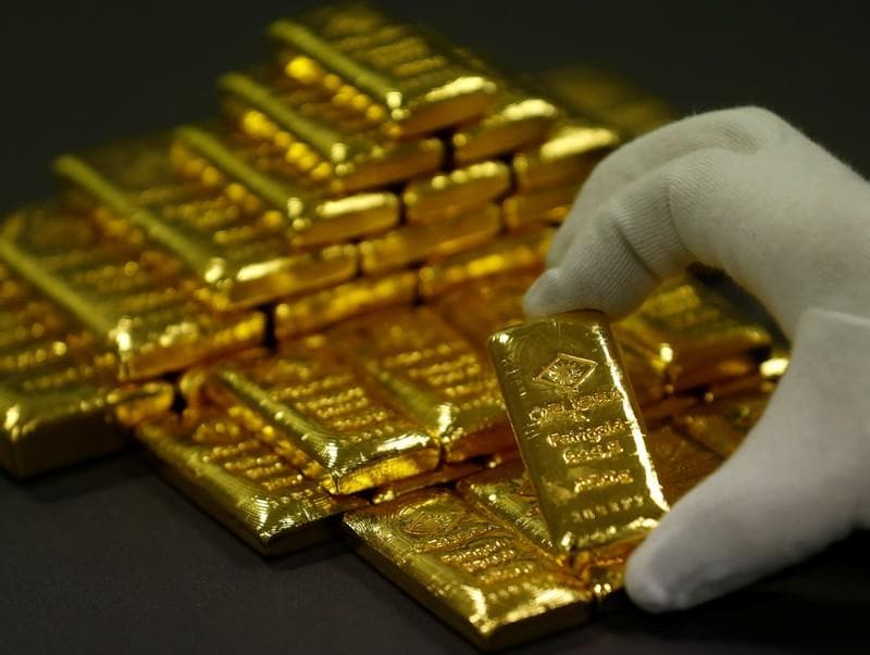 Gold edges lower as dollar gains after hawkish Fed minutes