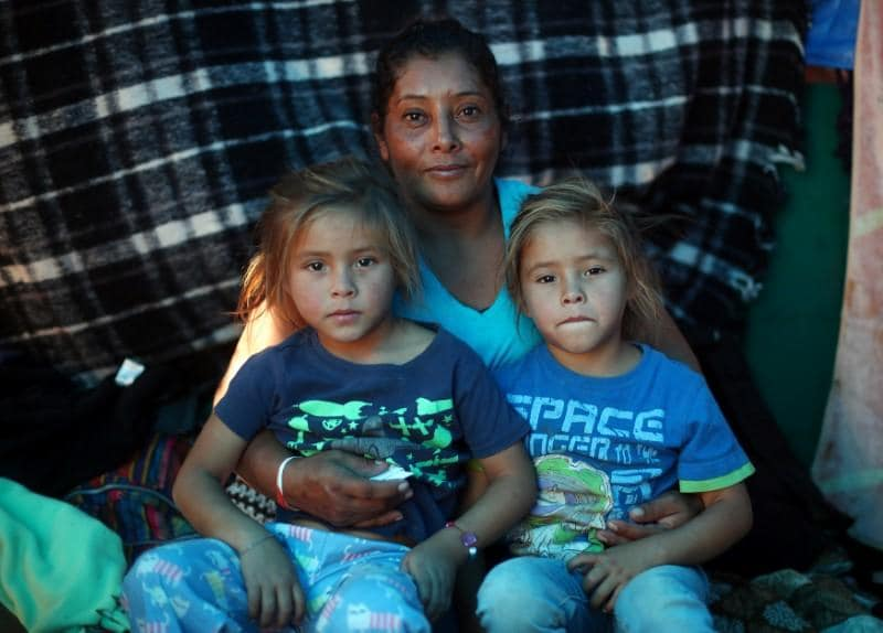 Honduran migrant clutching two small children flees tear gas